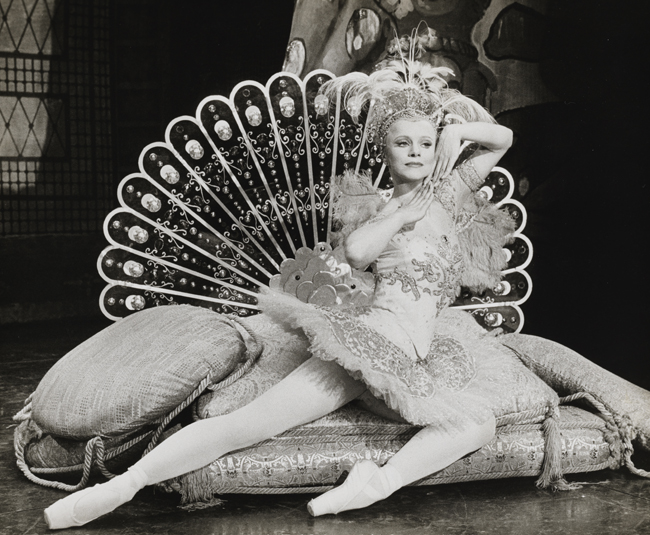 A ballerina in costume reclines on cushions with a stylized peacock tail fanned out behind her.
