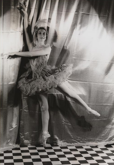 A ballerina, in costume, stands en pointe in front of a curtain on a checkerboard floor.