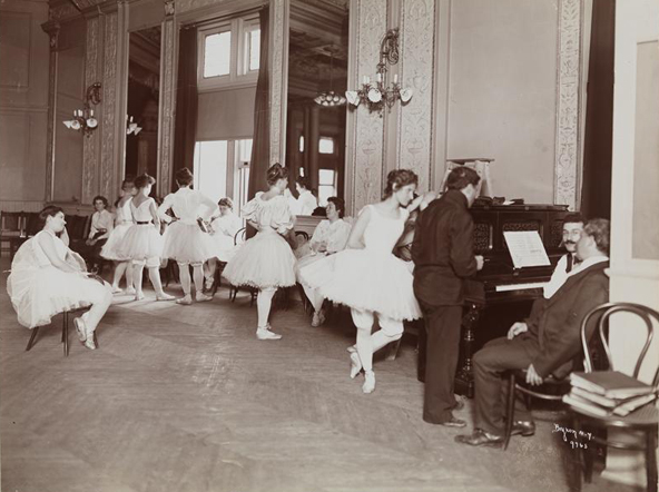 A group of ballerinas are gathered in a large room. In the background, some stand, and others sit. In the lower right, one ballerina leans against a piano with three gentleman, one standing, and two sitting at the instrument.