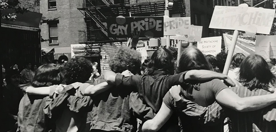Photograph by Fred W. McDarrah of a group of people with their arms around each other and holding signs related to Pride