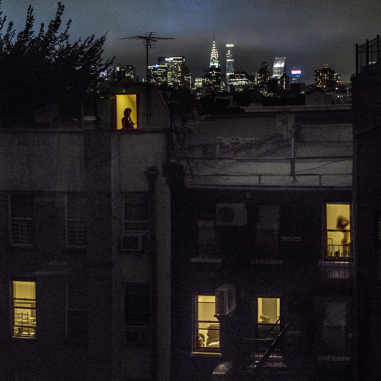 조명 된 창문이있는 밤 5 번가 이스트 XNUMX 번가에있는 Sally Davies의 백미러.