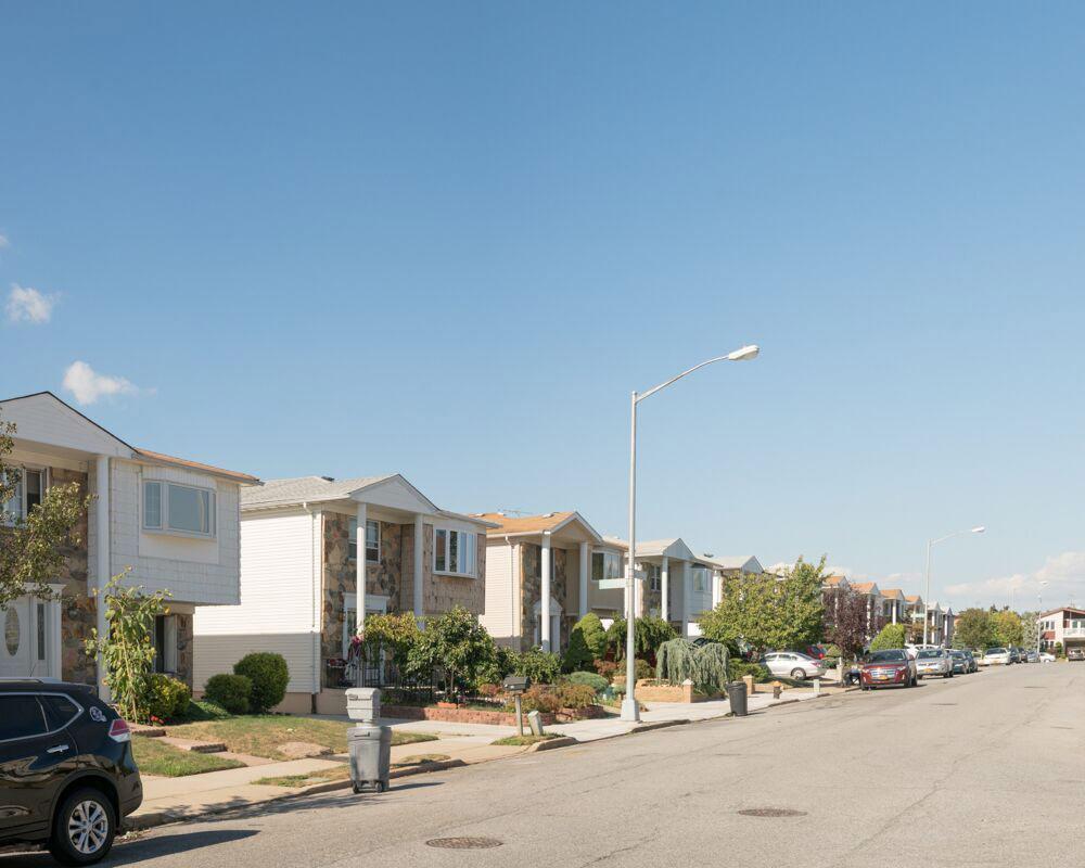 Una serie de casas idénticas de dos pisos se alinean en una calle.