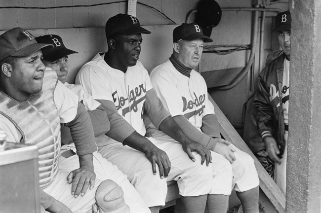 Jackie Robinson sits in the Dodgers' dugout with other players and manager Charlie Dressen during a game