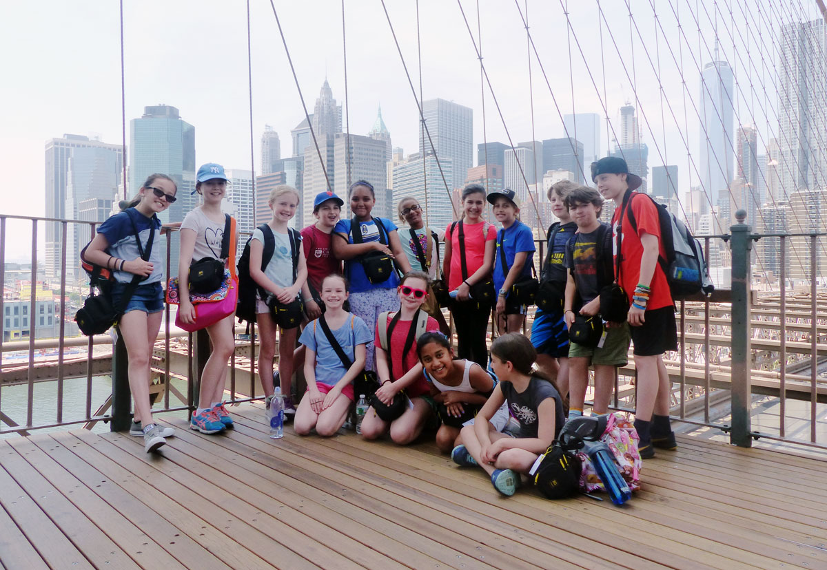 A group of students pose for a portrait on the Brooklyn Bridge