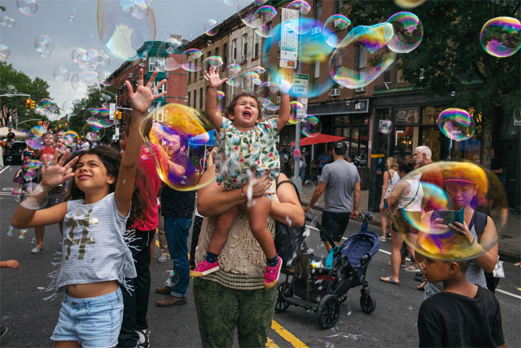 Members of the Park Slope community on the street playing with bubbles.