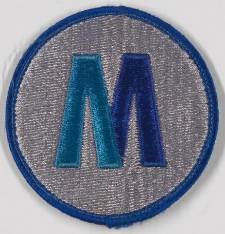 "Circular cloth patch bearing a capital letter ""M"" in two shades of blue on a field of white, trimmed in blue."