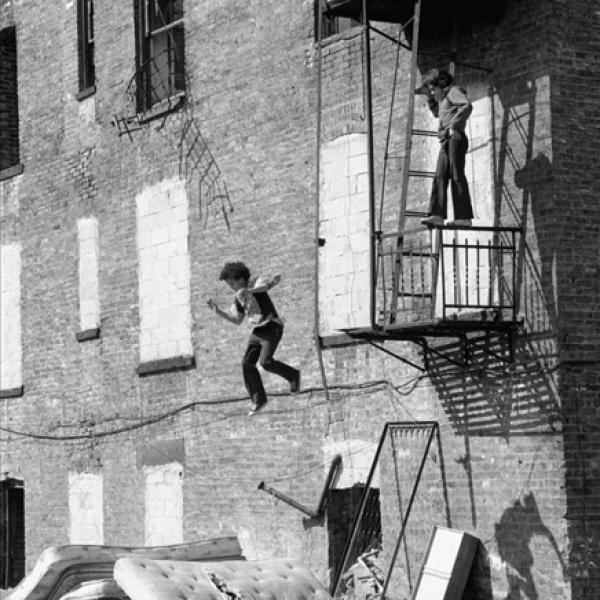 Uma fotografia de peça de rua de Martha Cooper, de um garoto pulando da escada de incêndio no Lower East Side.