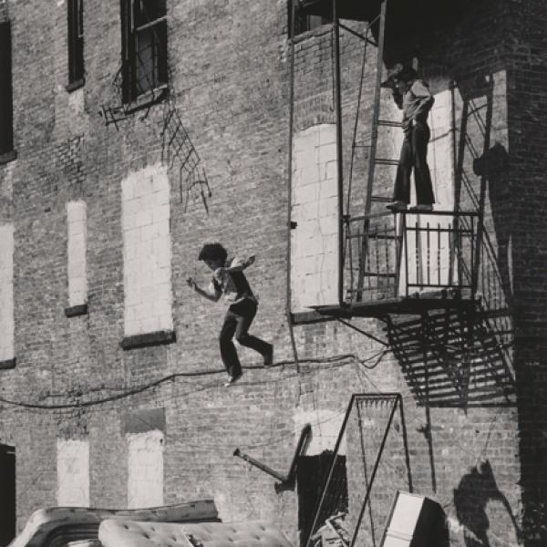れんが造りの建物の白黒写真。 少年は、古いマットレスの山に着く前に空中にいる別の少年を見下ろす、火災避難の手すりに立っています。