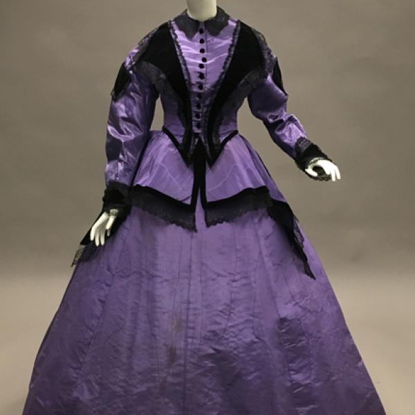 Um vestido de moiré de seda roxa de 1866, com veludo preto e detalhes em renda preta que pode ser usado durante o dia ou a tarde.