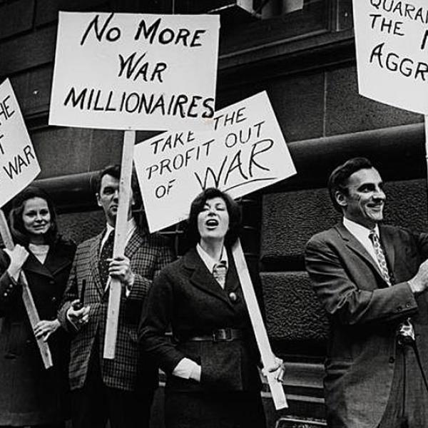 Fotografia em preto e branco mostra um grupo de homens e mulheres que protestam contra o envolvimento americano em conflitos no exterior. Os manifestantes estão segurando cartazes abordando suas preocupações.