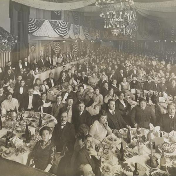 Black and white circa 1910 photograph of a formal dinner banquet. Men, women, and a few children sit at tables looking at camera, place settings, dessert, and wine bottles are visible on the tables.