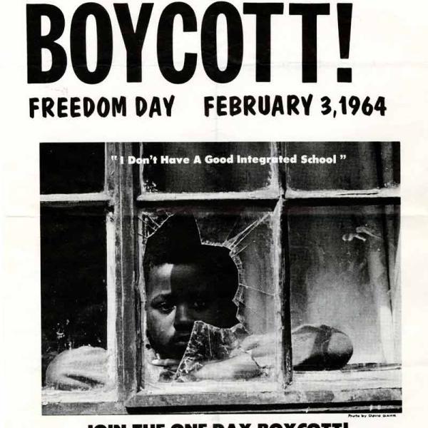 """A imagem mostra um panfleto para o boicote da escola em Nova York em 3 de fevereiro de 1964. O panfleto apresenta uma foto de um garoto negro olhando pela janela quebrada da escola. Abaixo da foto, há uma citação: """"Eu não tenho uma boa escola integrada""""."""