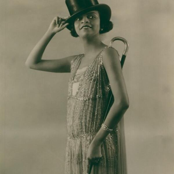 A black and white photograph of Florence Mills posed in a fancy dress with top hat and cane