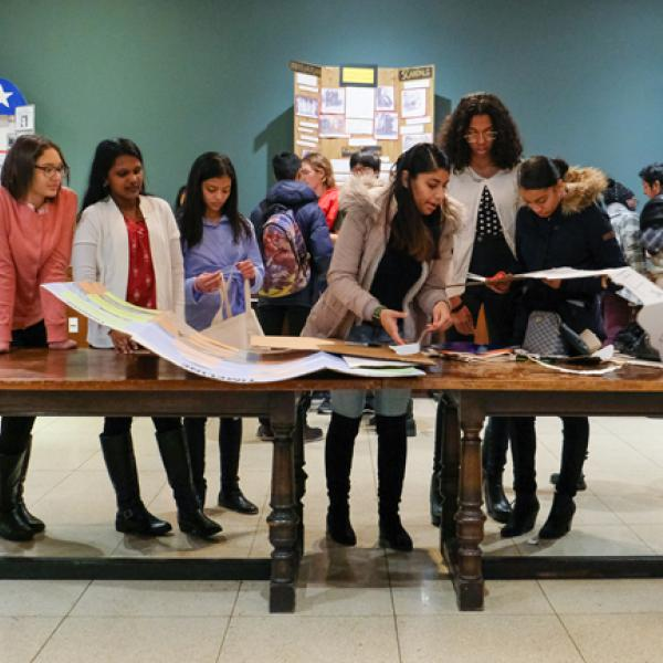 A group of students stand on one side of a long wooden table looking at documents and History Day projects.