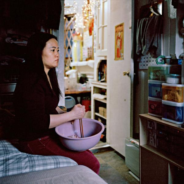 A Chinese woman stirs food in a bowl while watching a Chinese soap opera. She is sitting on a bed in an apartment.