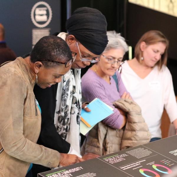 Teachers examining text in the exhibition Future City Lab