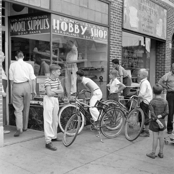 A group of boys, some with bikes, stand in front of the entrance to Long Island Hobby Shop