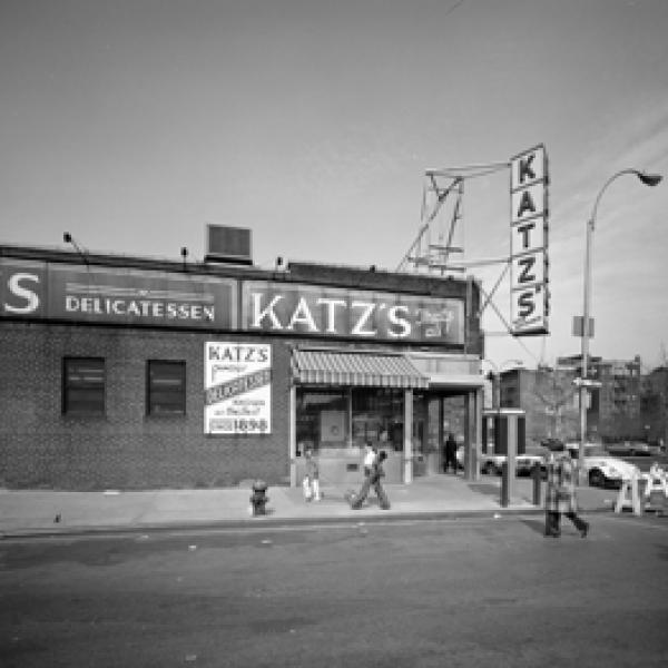 Vue extérieure de l'épicerie fine de Katz à l'intersection des rues Ludlow et Houston avec quelques personnes qui passent.