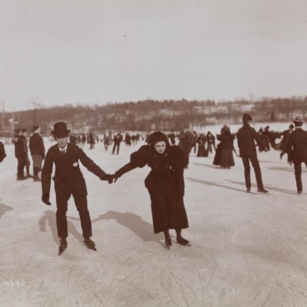 Uma foto de museu ao ar livre de um homem e mulheres de mãos dadas enquanto patina no gelo com um grupo de pessoas.