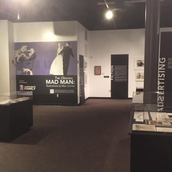 Uma fotografia de instalação de exposição de The Original Mad Man: Illustrations by Mac Conner.