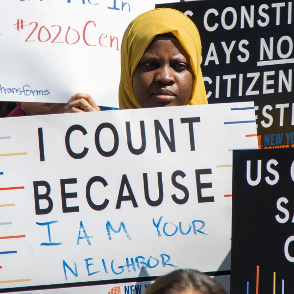 """Image shows a young person at a New York City Council press conference holding a sign reading """"I Count Because I Am Your Neighbor."""""""