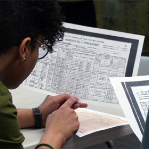 A teacher examines a completed 1900 census form in a workshop comparing the 1900 and 2020 census