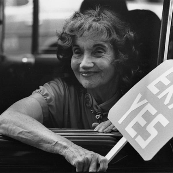"Alice Paul looks out of the window of a vehicle holding a sign that reads ""ERA YES"""