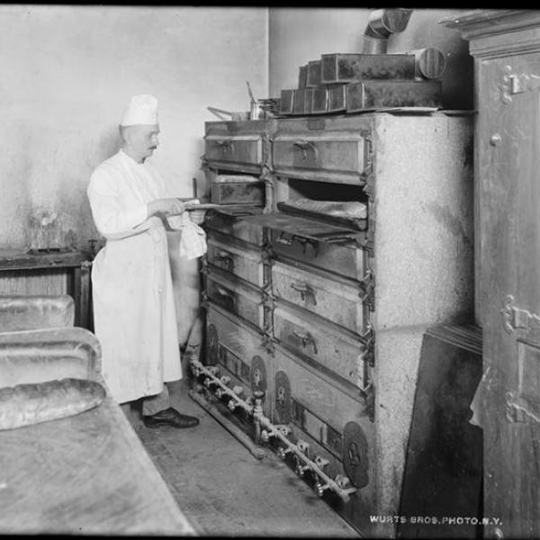 Uma foto de Wurts Bros. (Nova York, NY) de um chef de restaurante usando um forno de pão.