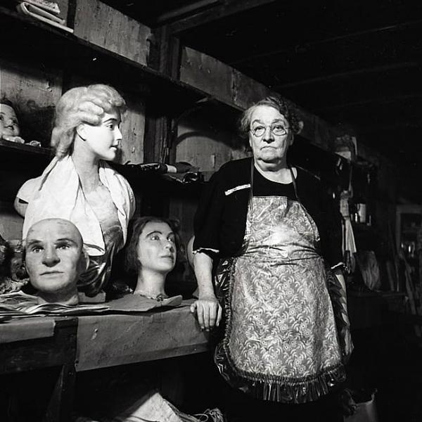 An older woman looks at the camera while surrounded by wax heads she created