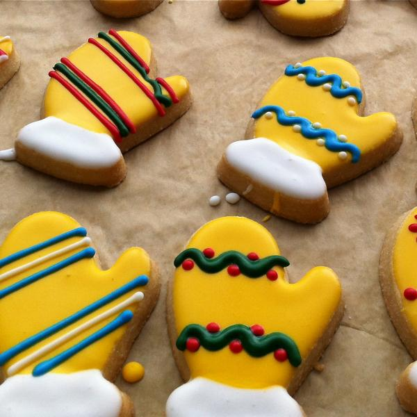 Mitten-shaped cookies decorated with yellow, red, blue, green and white icing in various patterns.