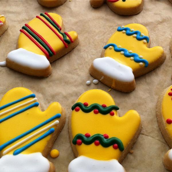 벙어리 모양의 쿠키는 다양한 패턴의 노란색, 빨간색, 파란색, 녹색 및 흰색 장식으로 장식되어 있습니다.