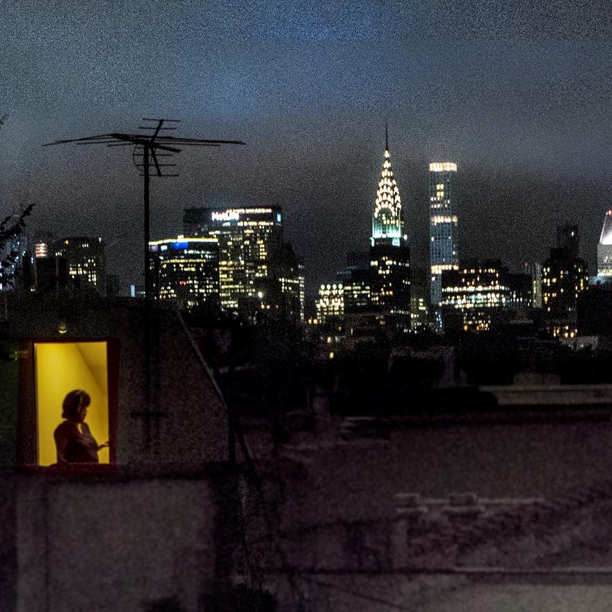 Retrovisor do apartamento de Sally Davies na East 5th Street à noite com janelas iluminadas.