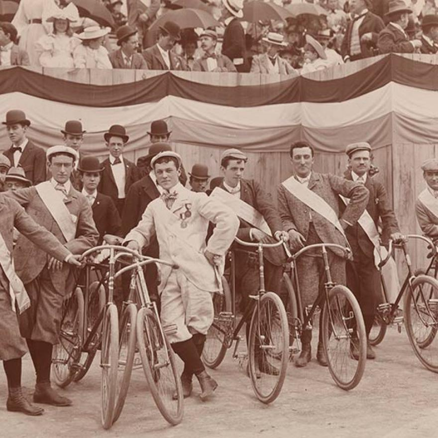 Men line up with their bicycles as spectators look on from raised seating before The Evening Telegram Bicycle Parade