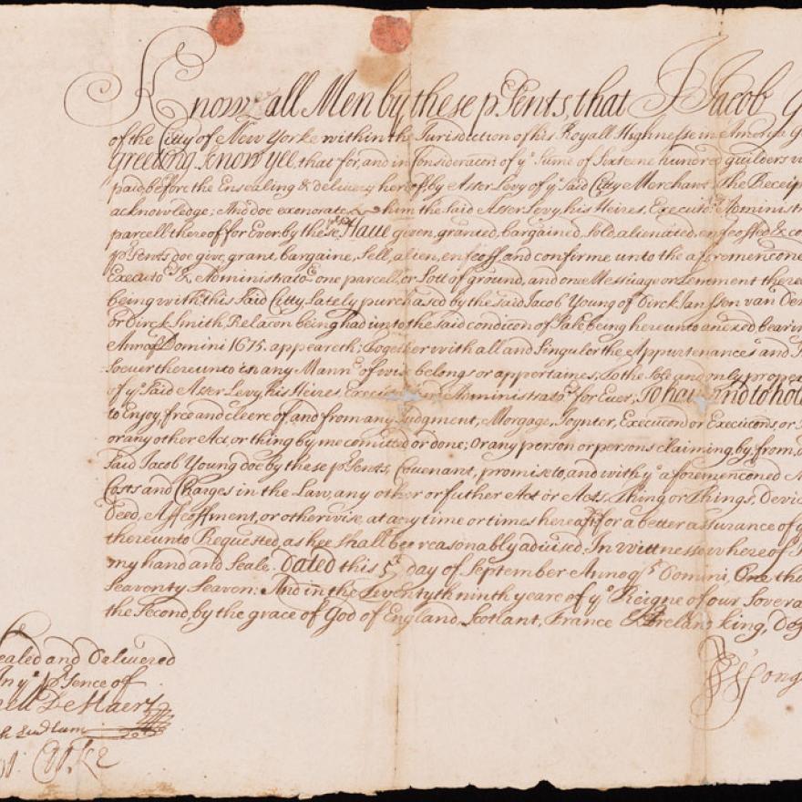Um velho pedaço de papel com elaborado roteiro e um lacre de cera no canto inferior direito