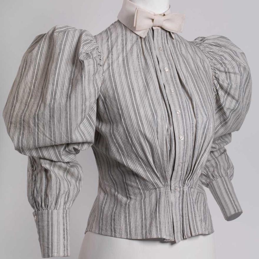 Camisa de algodão listrado cinza e branco com gola de linho amarrada em uma gravata borboleta