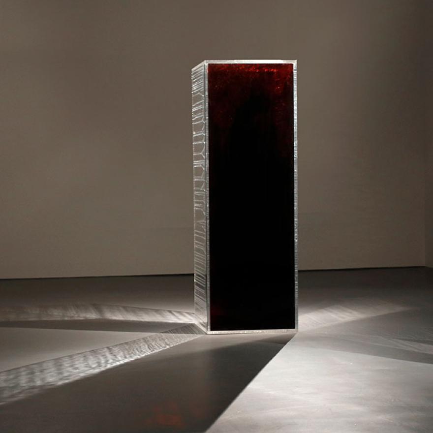 XNUMXつの側面が反射し、カメラに面する側面が血赤である長方形のプリズム。 光が反射しています
