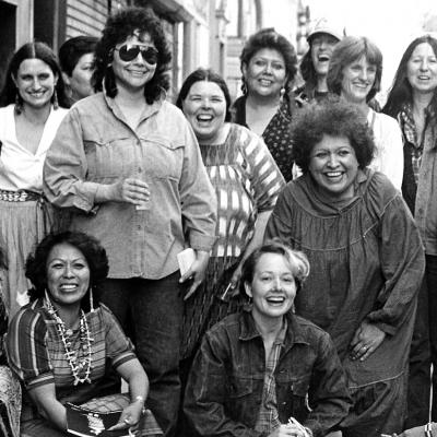 Photograph of artists from the exhibition, Women of Sweetgrass, Cedar and Sage, friends and community members outside the American Indian Community House Gallery taken in 1985.