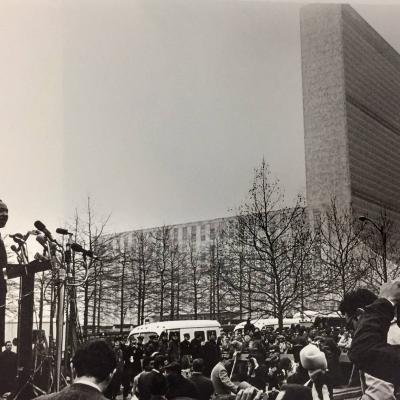 From an elevated platform, Rev. Martin Luther King Jr. addresses a gathered crowd of journalists in New York City