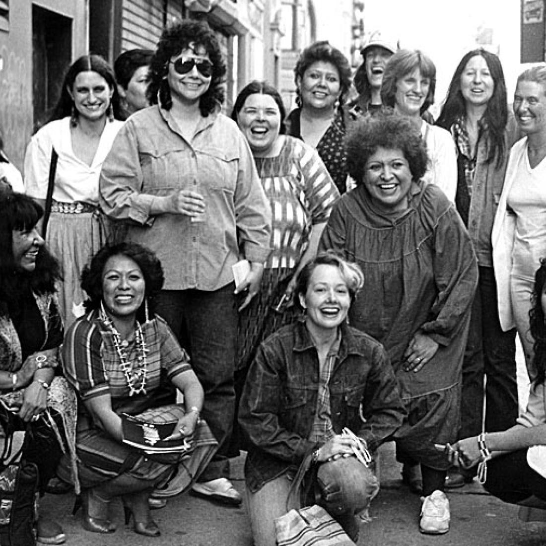 Fotografía de artistas de la exposición, Women of Sweetgrass, Cedar and Sage, amigas y miembros de la comunidad fuera de la American Indian Community House Gallery tomada en 1985.