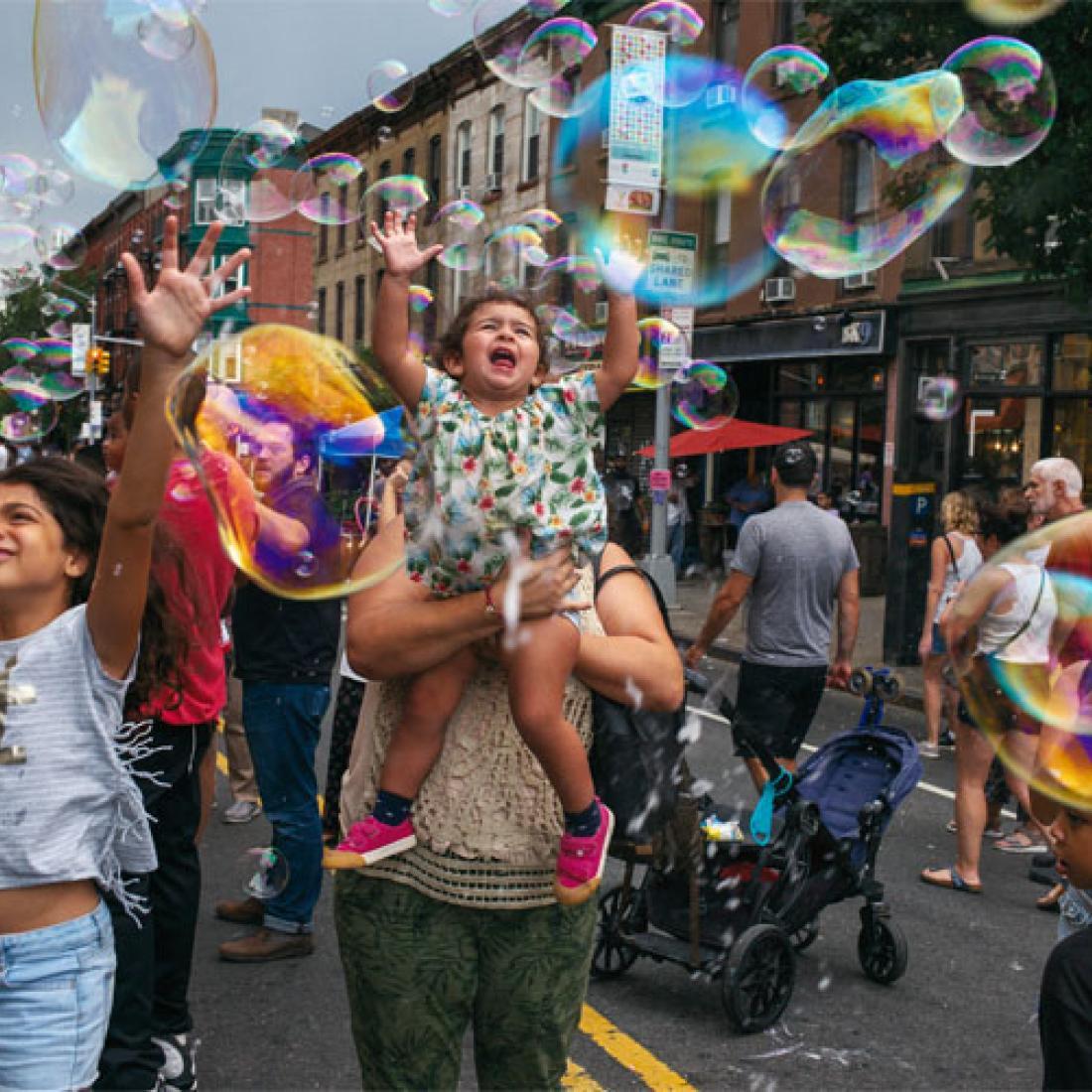 Membros da comunidade Park Slope na rua brincando com bolhas.