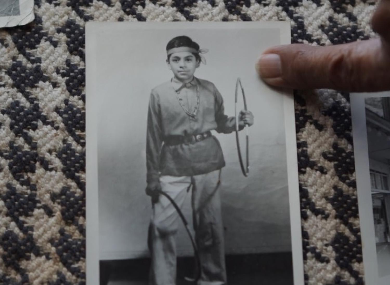 左手に輪を持ち、右脚に別の輪を持っているネイティブの少年の白黒写真。 指が写真を指しています。