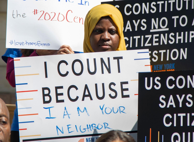 """이미지는 뉴욕시 의회 기자 회견에서""""나는 네 이웃이기 때문에 나는 셀 수 없다""""라는 표시를 들고있는 젊은이를 보여줍니다."""