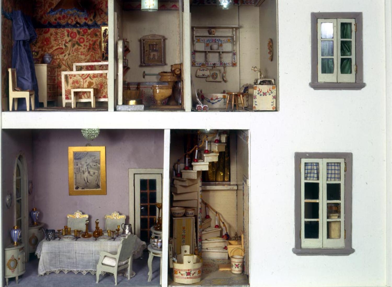 Vista de duas janelas, escadas e sala de jantar mobiliada, banheiro e quarto na casa de bonecas Stettheimer